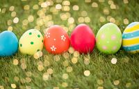 row of colored easter eggs on artificial grass