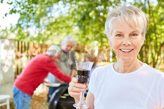 Seniorin mit Glas Wein auf einer Gartenparty