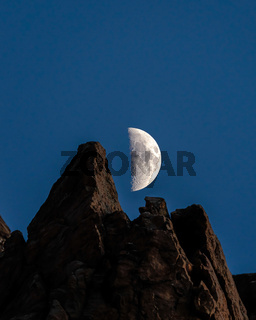 Half moon in the dark blue sky over rocky mountain in Provo Canyon Utah at night