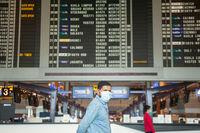 Singapur, Republik Singapur, Mann mit Mundschutz vor Anzeigetafel am Flughafen Changi