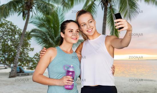 sporty women taking selfie by smartphone outdoors