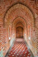 Wooden ancient door at the end of brick corridor