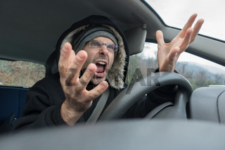 Angry man with screaming into car in winter time