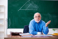 Old male math teacher in the classroom
