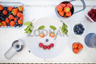 Smiling face made with berries and mint leaves on a plate