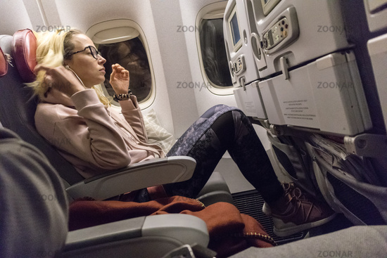 Sporty casual young blonde caucasian lady watching movie while traveling by airplane by the window. Commercial transportation by planes