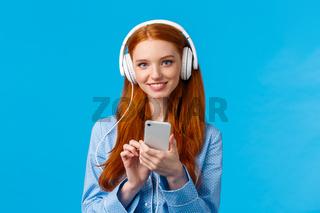 Tender and feminine, cute redhead female student, wearing headphones study lisening classical music, standing blue background, holding smartphone wearing nightwear