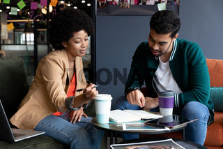 Happy diverse businessman and businesswoman drinking coffee on their break in office