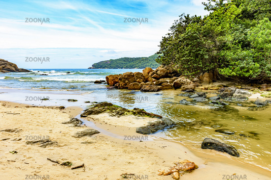 River flowing into the beach between the sea, the rocks and the rainforest in Trindade