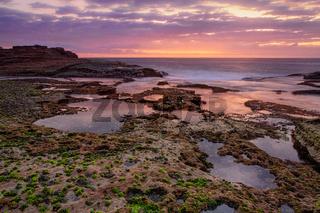 Coastal dawn skies at low tide exposing the rocky reef