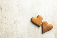 Two wooden hearts on vintage background.