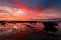 Sunrise seascape at low tide with vivid reflections