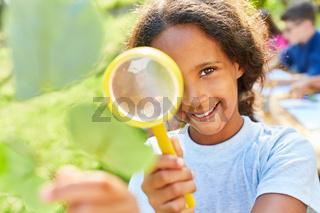 Mädchen im Ferienlager schaut durch Lupe auf ein Blatt
