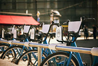 standing in a number of bicycles for hire on a city street