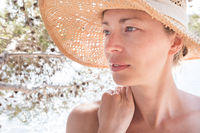 Close up portrait of no makeup natural beautiful sensual woman wearing straw sun hat on the beach in shade of a pine tree