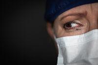 Tearful Stressed Female Doctor or Nurse Wearing Medical Face Mask on Dark Background