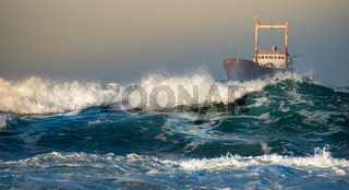 Abandoned ship in the stormy ocean with big wind waves during sunset. Paphos Cyprus