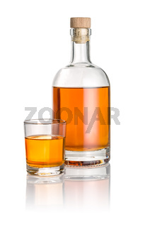 Bottle and drinking glass filled with amber liquid
