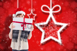 Composite image of woman holding a christmas present