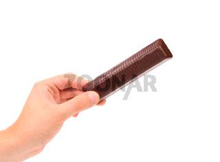 Hand holds bar of chocolate.