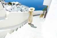 Young woman in a white dress and straw hat, walking at the city of Oia, island of Santorini, Greece