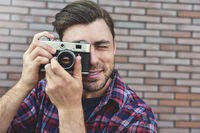Say cheese, hipster fashion photographer man holding retro camera