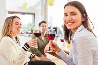 Gruppe Frauen als Freundinnen reden bei Glas Rotwein