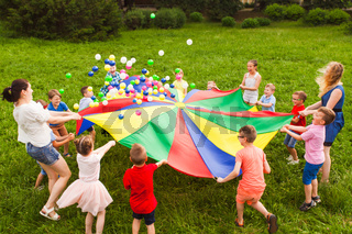 Birthday games on fresh air with parachute and balls