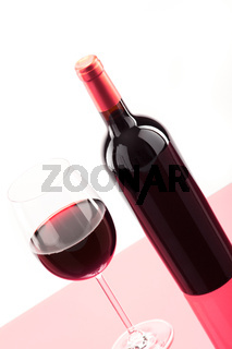 A glass of red wine with bottle