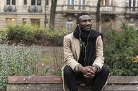 Handsome Black Man Sitting on Public Park Bench Backrest