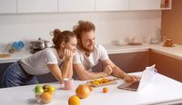 Young couple cooking healthy food in kitchen at home. Girl leaned on man smiling watching romantic movie. Beautiful young couple talking on video call using laptop