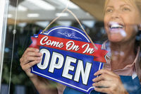 Happy Female Store Owner Turning Open Sign in Window