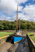 Fishing boat beached in mud by tidal River Tamar in Devon