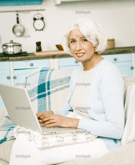 White haired italian woman use laptop for social media