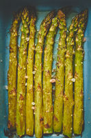 Close up with selective focus on roasted asparagus seasoned with salt, pepper, garlic.