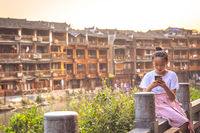 Young girl texting in Fenghuang