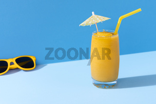 Mango smoothie and sunglasses. Tropical summer concept.