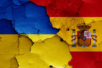flags of Ukraine and Spain painted on cracked wall