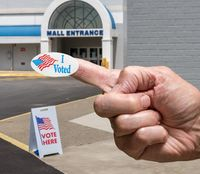 Hand with sticker by entrance to a polling place for elections in old Mall