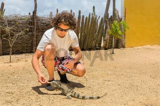 Young dutch man feeding iguana on ground