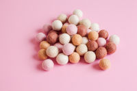 Pale of soft wool balls on pink background