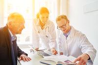 Arzt und Ärztin schauen in medizinisches Lexikon