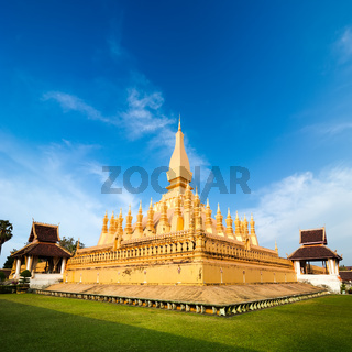 Golden buddhist pagoda of Phra That Luang Temple under blue sky. Vientiane, Laos travel landscape and destinations