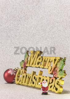 Cute tiny figurine of Santa Claus on a glitter silver snow background with the