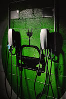 Electric vehicle charging station, free parking place green colored painted on wall symbol close up, no people