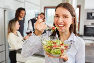 Junge Frau beim Salat essen in WG Küche