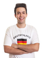 Laughing german sports fan with crossed arms and black hair