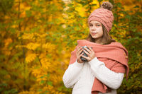 Girl drinking cocoa in autumn park