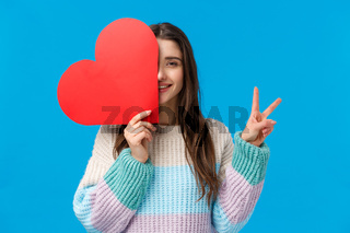 Waist-up portrait pretty feminine young romantic woman, made big cute red heart card on valentines day, hold it over face, show peace sign and smiling joyfully, express love and cherish relationship