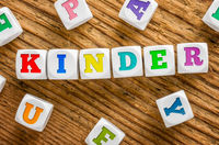 Letter dice on a wooden background - Kids - Kinder German